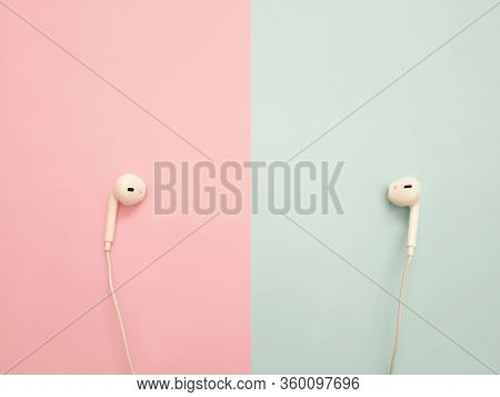 White Earphones On Pink And Blue Background. Earphones For Listening To Music And Sound On Portable