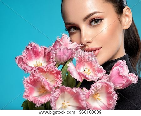 Beautiful white girl with flowers. Stunning brunette girl with big bouquet flowers of pink tulips. Closeup face of young woman with a healthy clean skin. Pretty woman with bright makeup