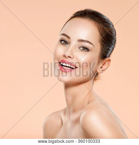 Portrait of smiling young woman with clean face. Close-up face with a smile of young adult woman with clean skin. Front portrait of woman with beauty face.