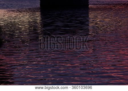 Saturated Ripple Surface Of Water On Sunset In Dark Colorful Color Of Purple, Orange, Golden Color,