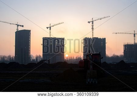 Excavator At Construction Site On A Background Of A Construction Cranes And Building. Dig The Ground