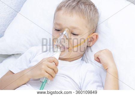 Boy With An Inhaler Mask - Respiratory Problems In Asthma. A Boy With An Inhaler Mask Lies In Bed An