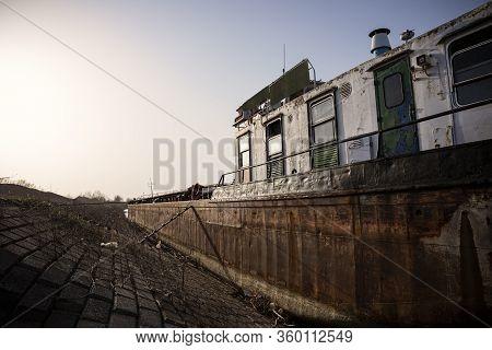 Shipwreck Abandoned And Stranded At The River Bank