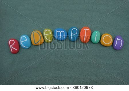 Redemption Word Composed With Multi Colored Stone Letters Over Green Sand