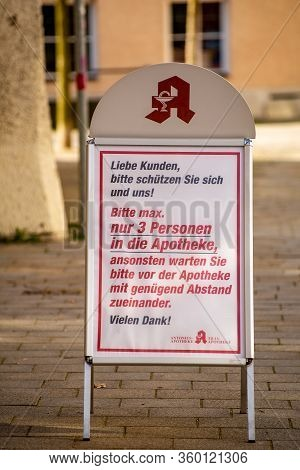 Altoetting,germany-april 1,2020: A Sign In German Outside A Pharmacy Asks People To Protect The Phar