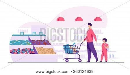 Father And Son Buying Food In Supermarket. Young Man And Boy Wheeling Shopping Cart With Food Along