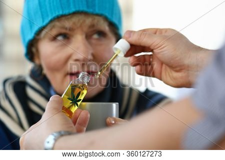 Close-up Of Elderly Woman Receives Sedative Drops From Doctor. Glass Bottle With Leaf Sign. Prescrip