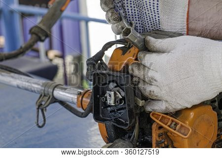 The Master In Working Gloves Repairs The Engine Of The Old Gas Trimmer Unscrews The Spark Plug With