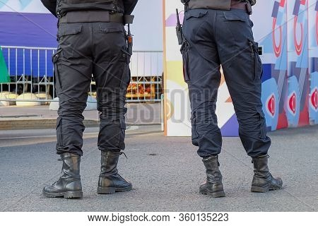 The Back View Of Police Officers Wearing Black Uniform Patrolling Streets With Walkie-talkie. Securi