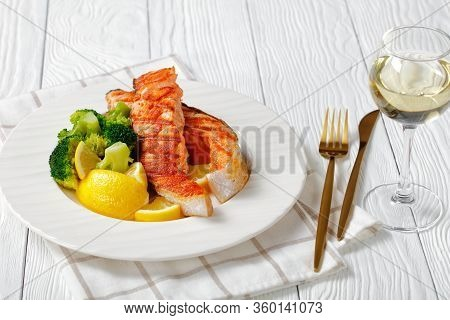 Grilled Atlantic Salmon With Boiled Broccoli, Lemon Wedges On A White Plate Served On A White Plate