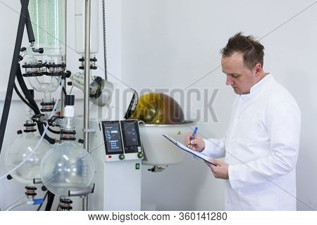 Scientist Holding Paper Board And Controlling Rotational Vaporizer During Cbd Oil Extraction. Machin