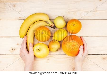 Orange, Yellow, Green Fruits In Female Hands Flat Lay On Wooden Background Top View. Oranges, Apples