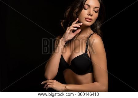 Attractive, Sexy Girl In Black Bra Touching Face While Posing Isolated On Black