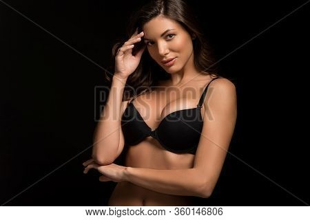Sensual, Sexy Girl In Black Bra Touching Head While Looking At Camera Isolated On Black