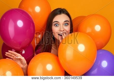 Smiling Surprised Caucasian Girl Posing With Bright Color Air Balloons On Yellow Background. Beautif