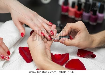 Manicure. Closeup Of Beautiful Woman Hands Polishing Nails With Red Nail Polish In Beauty Salon. Clo