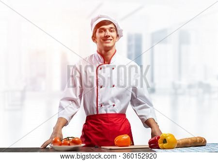 Young Smiling Chef Standing Near Cooking Table With Fresh Vegetables. Pleased Chef In White Hat And