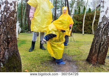 Mother With Cute Adorable Caucasian Siblings Children In Bright Yellow Raincoat And Wellies Playing