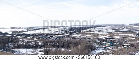 Russian Village Located In Early Spring. Landscape Of Early Spring, Snow Begins To Melt, Fields Open