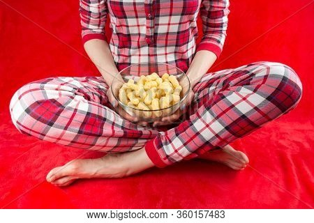 A Woman In A Red Checked Home Suite With A Dish Of Sweet Corn Sticks At Home On A Red Background In