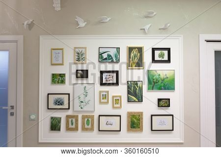 Many Photo Frames Are Hanging On The Wall. Frames Between Two Interior Doors. The Wall Is Decorated