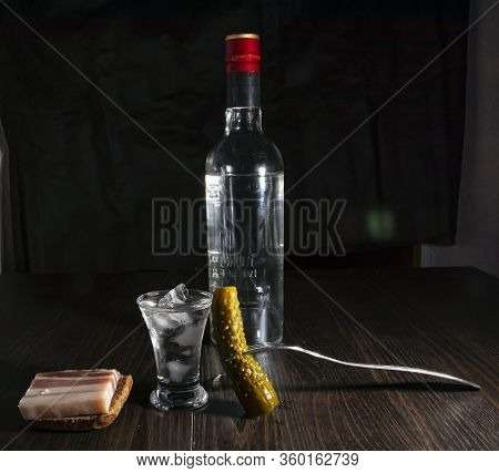 Bottle Of Vodka, Misted Glass With Cold Vodka On A Wooden Board With Bacon And Pickled Cucumbers.