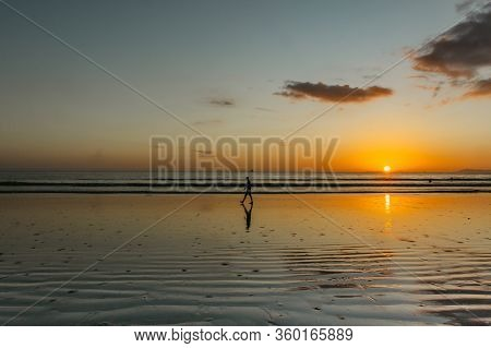 Silhouette Of A Man Walking On The Beach At Sunset. Clouds, Sea And Sandy Beach. Romantic Evening By