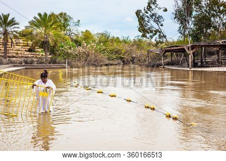 QASR El-YAHUD, ISRAEL - MARCH 2, 2020: Baptism ceremony. Woman in a white baptismal shirt enters the water of Jordan river. The site of the baptism of Jesus Christ. The concept of pilgrimage