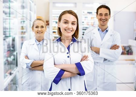 Cheerful Three Pharmacists Waiting For Customers In A Drugstore