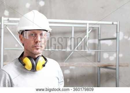 Portrait Of Man Construction Worker With Safety Hard Hat, Hearing Protection Headphones And Protecti