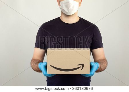 Amazon Delivery. Delivery Man Holding Cardboard Boxes In Medical Rubber Gloves And Mask. Copy Space.