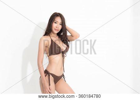 Beautiful Asian Woman With Long Brown Hair Wearing Brown Bikini Dress In A Summer Fashion Posing Stu