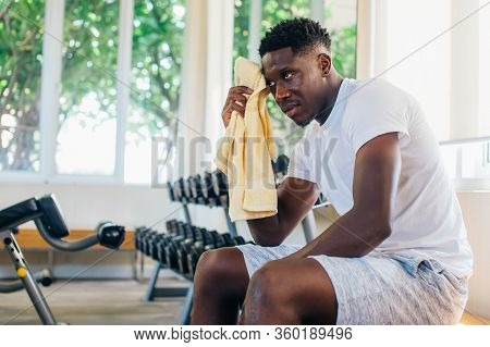 African American Sportsman Sitting On Bench And Wiping Sweat With Towel. Black Athlete Resting Durin