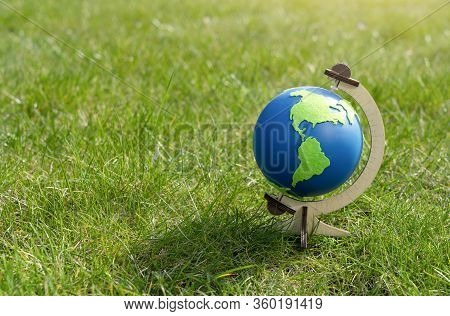 Globe Of The Planet Earth Standing On Green Grass In Sunny Day On Spring Or Summer, Eco Symbol, Gree