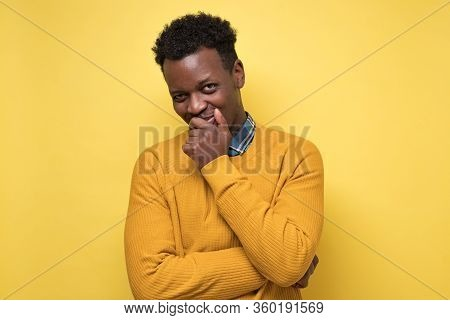 Young African American Man In Yellow Sweater Contemplating A Plan Hiding Smile.
