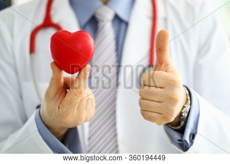 Male Medicine Doctor In Hold Red Toy Heart And Show Ok Or Approval Sign With Thumb Up Closeup. Cardi