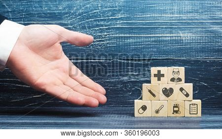 A Man Presents Blocks With Medical Attributes. Healthcare And Medical Insurance Concept. Providing H