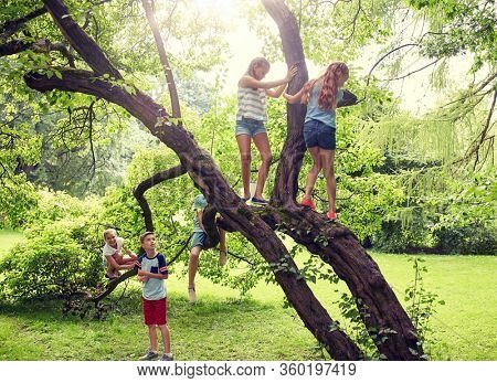 friendship, childhood, leisure and people concept - group of happy kids or friends climbing up tree and having fun in summer park