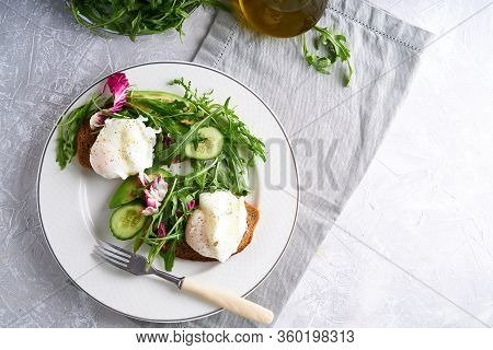 Poached Eggs With Herbs, Avocado And Cucumber Served On A Plate On A Light Background Copy Space