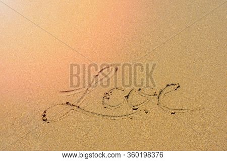 Yellow Sand On Mediterranean Sea Shore With Foamy Wave And Written Word