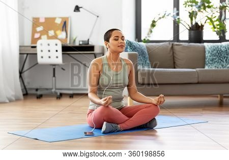 mindfulness, spirituality and healthy lifestyle concept - african american woman in earphones listening to music on smartphone and meditating in lotus pose at yoga studio