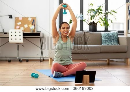 fitness, sport and healthy lifestyle concept - happy smiling african american woman with tablet pc computer and dumbbells exercising at home
