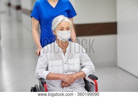 medicine, health safety and pandemic concept - nurse carrying senior woman patient in wheelchair wearing face protective medical mask for protection from virus disease at hospital corridor