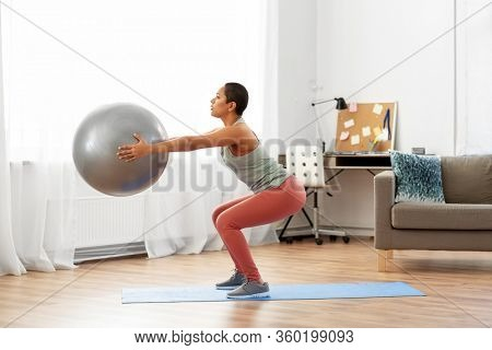 fitness, sport and healthy lifestyle concept - african american woman exercising and doing squats with ball at home