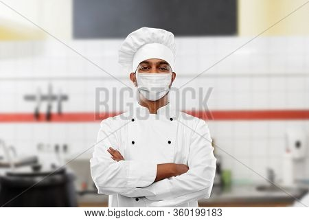 health, safety and pandemic concept - indian male chef cook in toque with crossed hands wearing face protective medical mask for protection from virus disease at restaurant kitchen