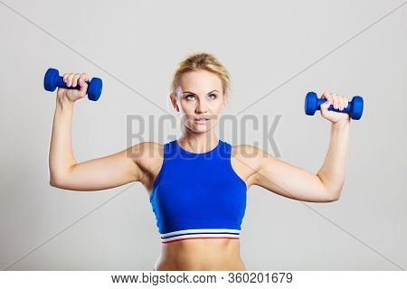 Sporty Woman Lifting Light Dumbbells Weights. Fit Girl Exercising Building Muscles. Fitness And Body