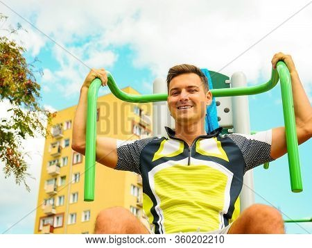 Young Handsome Man Working Out In Outdoor Gym. Sporty Guy Flexing His Muscles On Machine. Staying Fi