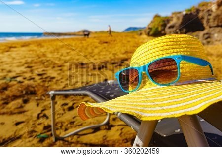 Summer And Holidays, Resting On Seaside. Blue Sunglasses And Yellow Straw Hat On Sandy Beach Sea Sho