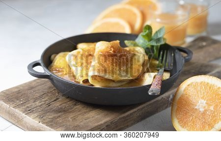 Crepes With Orange Sauce In A Cast Iron Pan. Traditional French Crepe Suzette With Orange Sauce.