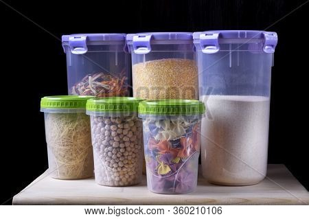 Variety Of Groats And Pasta In Plastic Jars On The Wooden Shelf. Concept Of Loading Up On Non-perish